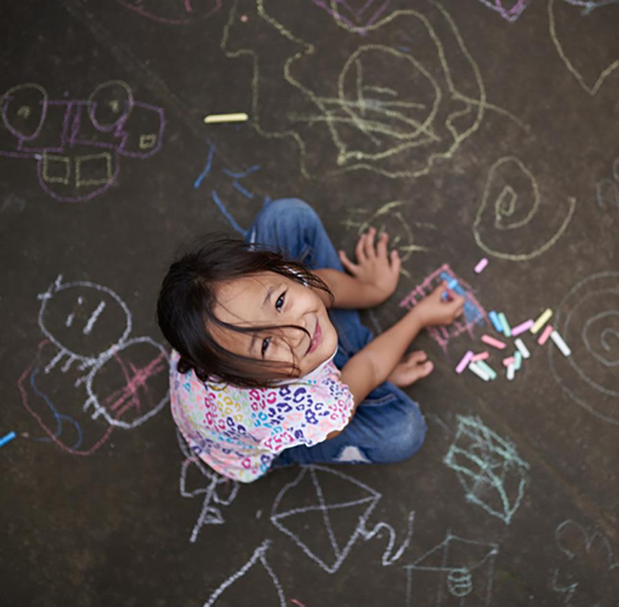 girl making chalk drawings on pavement