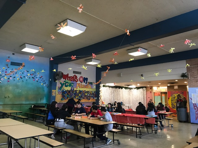 lunchroom with colorful murals and paper birds hanging from ceiling